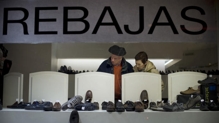 A couple look in a shoe shop offering discounts after Christmas, in Pamplona, northern Spain, Monday, Jan. 7, 2013. Spain is in the throes of its second recession in just over three years, with its economy battered by a collapse in the once-key real estate sector. (AP Photo/Alvaro Barrientos)
