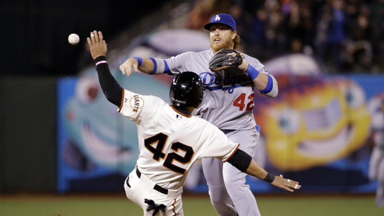 Los Angeles Dodgers second baseman Justin Turner, top, turns a double play over San Francisco Giants' Gregor Blanco after a ground ball by Brandon Hicks during the eighth inning of a baseball game on Tuesday, April 15, 2014, in San Francisco. (AP Photo/Marcio Jose Sanchez)