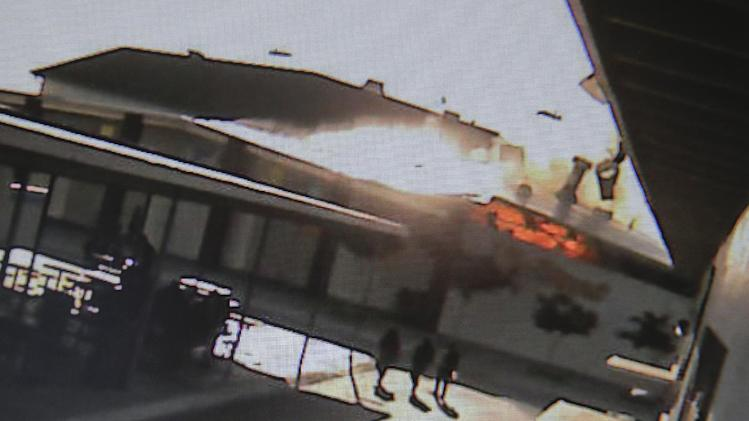 In this still image taken from a security camera show students at Santa Ana High School reacting during a explosion in the boiler room Tuesday, June 11, 2013 in Santa Ana, Calif. The explosion happened near the school's gym and it caused significant structural damage to the building but no injuries. (AP Photo)