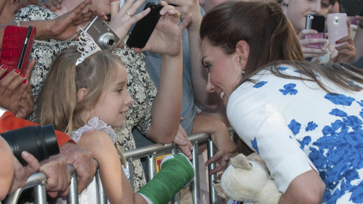 Kate, the Duchess of Cambridge, right, meets a young member of the public after attending a reception at the Brisbane Convention & Exhibition Centre, in Brisbane, Australia Saturday, April 19, 2014. (AP Photo/John Pryke, Pool)
