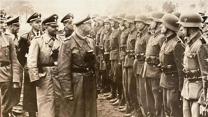 The June 3, 1944 photo provided by the US Holocaust Memorial Museum shows Heinrich Himmler, centre,  SS Reichsfuehrer-SS, head of the Gestapo and the Waffen-SS, and Minister of the Interior of Nazi Germany from 1943 to 1945, as he reviews troops of the Galician SS-Volunteer Infantry Division   Michael Karkoc  a top commander whose Nazi SS-led unit is blamed for burning villages filled with women and children lied to American immigration officials to get into the United States and has been living in Minnesota since shortly after World War II, according to evidence uncovered by The Associated Press. Michael Karkoc became a member of the Galician division after the Ukrainian Self Defense Legion was incorporated into it near the end of the war. (AP photo/ U.S. Holocaust Memorial Museum, courtesy of Atlantic Foto Verlag Berlin)
