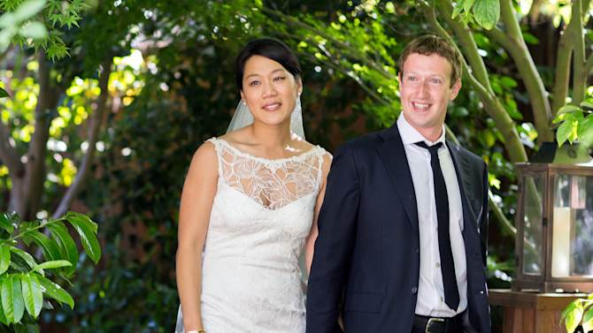 """This photo provided by Facebook shows Facebook founder and CEO Mark Zuckerberg and Priscilla Chan at their wedding ceremony in Palo Alto, Calif., Saturday, May 19, 2012. Zuckerberg updated his status to """"married"""" on Saturday. The ceremony took place in Zuckerberg's backyard before fewer than 100 guests, who all thought they were there to celebrate Chan's graduation. (AP Photo/Facebook, Allyson Magda Photography)"""