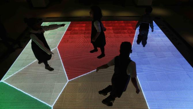 "Children run across an interactive exhibit at the new National Museum of Mathematics in New York, Monday, Dec. 17, 2012. The museum is aimed at kids aged 8 to 13, and curators have given the place a playground feel. The 40 exhibits include a ""wall of fire"" made up of laser lights that teaches kids about geometry and a square-wheeled tricycle that still manages to produce a smooth ride thanks to a wavy track. (AP Photo/Seth Wenig)"