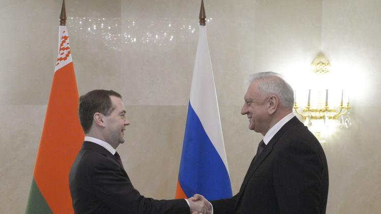 Russia's PM Medvedev shakes hands with his Belarus counterpart Myasnikovich in Moscow