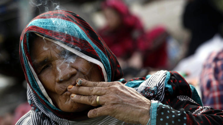A supporter of Tahirul Qadri, a Pakistani-Canadian cleric, smokes as she continues her sit-in protest for the sixth day in Islamabad, Pakistan, August 20, 2014. (EPA/BILAWAL ARBAB)