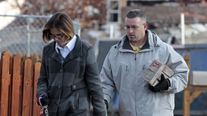 Brett and Nikki Cocherell carry a section the brick wall of their home that was being demolished in Indianapolis, Tuesday, Nov. 27, 2012.  City building inspectors last week ordered the demolition of 29 houses by Dec. 20. Four other homes, including two that were leveled in the Nov. 10 explosion, are being maintained as police investigate what they believe was an intentional natural gas explosion.  (AP Photo/Michael Conroy)