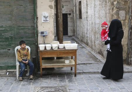 A woman carries a child as she walks past a boy selling yogurt along a street in Aleppo's Bab al-Hadeed district
