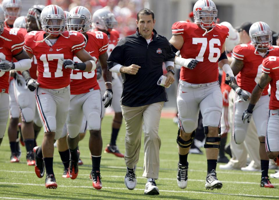 Ohio State head coach Luke Fickell, cetner, leads his team onto the field to face Akron in an NCAA college football game in Columbus, Ohio on Saturday, Sept. 3, 2011.  (AP Photo/Jay LaPrete)