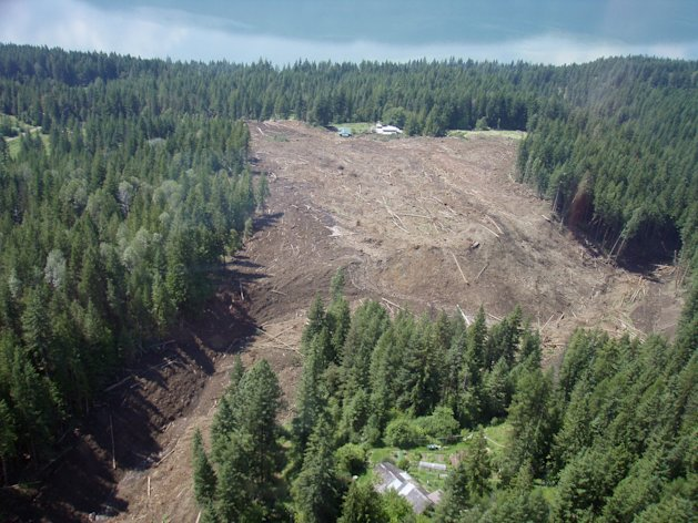 The Johnsons landing landslide is shown in this Thursday July 12, 2012 photo provided by Emergency BC. Four people are still unaccounted for nearly 24 hours after a wall of rock, mud and trees cascaded down the side of a mountain above the shores of Kootenay Lake, tearing through the tiny community of Johnsons Landing, about 70 kilometres northeast of Nelson. At least three homes in the southeastern B.C. hamlet are engulfed by the muck, which is unstable and shifting, prompting searchers to call off rescue efforts at least once on Thursday afternoon. Emergency crews met at dawn Friday to consider the most efficient and effective way to search the massive mudslide for possible victims. (AP Photo/Emergency BC via The Canadian Press)