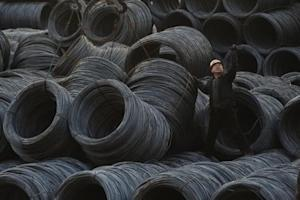 A labourer works on piles of steel coils in Taiyuan, Shanxi province