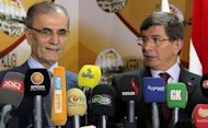 Turkish Foreign Minister Ahmet Davutoglu (right) and the governor of Kirkuk, Najm al-Din Omar Karim, give a joint press conference following their meeting in the disputed northern Iraqi city of Kirkuk on August 2. Davutoglu visited the city without informing Baghdad, infuriating Iraq and bringing relations to a new low