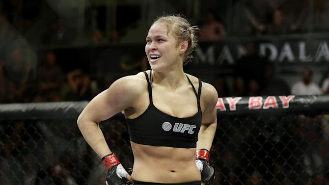 In this Feb. 22, 2014, file photo, Ronda Rousey looks around after defeating Sara McMann in a UFC 170 mixed martial arts women's bantamweight title bout in Las Vegas. Gina Carano was scheduled to meet with UFC President Dana White on Wednesday April 9, to discuss a return to mixed martial arts for a potential bout with bantamweight champion Rousey