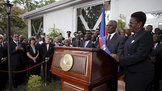 Provisional Haitian president Jocelerme Privert gives his inauguration speech accompanied by his wife Ginette in the gardens of the National Palace in Port-au-Prince