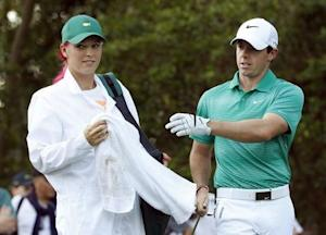 Tennis player Wozniacki of Denmark works as the caddie for her boyfriend McIlroy of Northern Ireland during the Par 3 Contest at the Augusta National Golf Club in Augusta