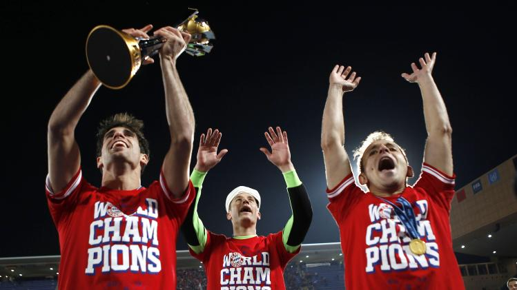 Javier Martinez of Germany's Bayern Munich holds the trophy as he celebrates with goalkeeper Manuel Neuer and Rafinha after winning their 2013 FIFA Club World Cup final soccer match against Morocco's Raja Casablanca at Marrakech stadium