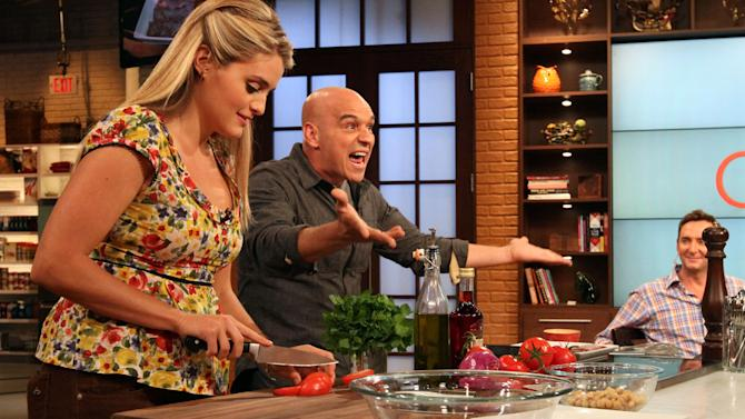 """This Friday, Aug. 26, 2011 photo shows co-hosts Daphne Oz, left, and Iron Chef Michael Symon as they prepare food while Clinton Kelly, right, looks on during a rehearsal of ABC's """"The Chew"""" in New York. Can some of food and style TV's biggest stars help ABC soap fans get over cancellation of their favorite stories? The network's counting on it for """"The Chew.""""     (AP Photo/Tina Fineberg)"""