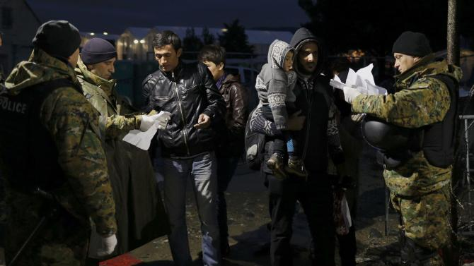 Migrants have their documents checked by Macedonian Police officers as they cross the border from Greece into Macedonia, near Gevgelija