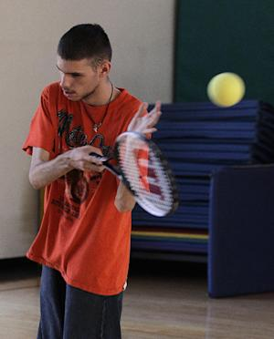 In this photo taken Oct. 16, 2012, Austin Benavidez, who is blind, practices his tennis serve using an oversized ball filled with ball bearings at the California School for the Blind in Fremont, Calif. Students at the school are learning to play tennis, and expanding the boundaries of what the blind can do while offering new insights into the human mind. They must turn their ears into eyes, listening for the ball's bounce to figure out where to swing their rackets. (AP Photo/Ben Margot)