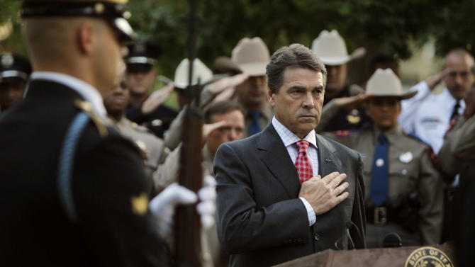 """Texas Governor Rick Perry and law enforcement personnel observe the playing of """"TAPS"""" during a memorial service at the Texas State Cemetery Twin Towers Monument in Austin, TX, Sunday, Sep. 11, 2011.  America observed the 10th anniversary of the Sep. 11, 2001 terrorist attacks with remembrance services around the country.  (AP Photo/Erich Schlegel)"""
