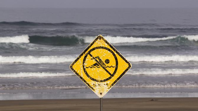 A no swimming sign is displayed at Muriwai Beach near Auckland, New Zealand, Thursday, Feb. 28, 2013, a day after Adam Strange was killed by a shark. About 150 friends and family of Strange, 46, wrote messages to him in the sand and stepped into the water Thursday at a New Zealand beach to say goodbye after he was killed Wednesday by a large shark. (AP Photo/New Zealand Herald, Brett Phibbs) New Zealand Out, Australia Out