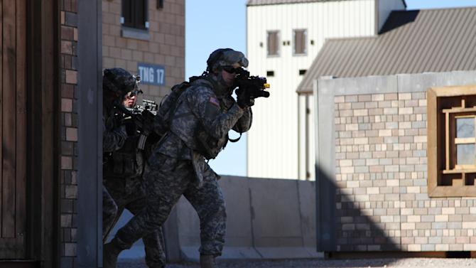 Two soldiers move out of a building during a training exercise in Ft. Bliss, Texas, Wednesday, Jan. 23, 2013. The army is rolling out a new training platform that allows the integration of live units, simulators and computer generated forces. It is expected to allow cheaper, more frequent training. (AP Photo/Juan Carlos Llorca)