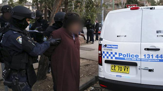 Handout shows police officers detaining a man during early morning raids in western Sydney, Australia