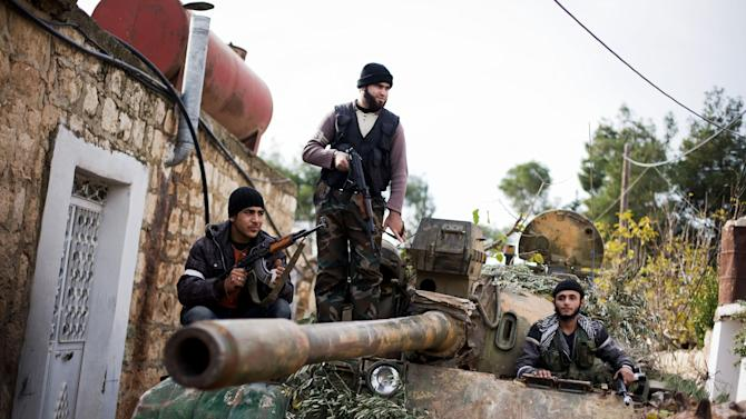 Kurdish members of the FSA are seen on a tank stolen from the Syrian Army in Fafeen village, north of Aleppo province, Syria, Wednesday, Dec 12, 2012 (AP Photo / Manu Brabo)