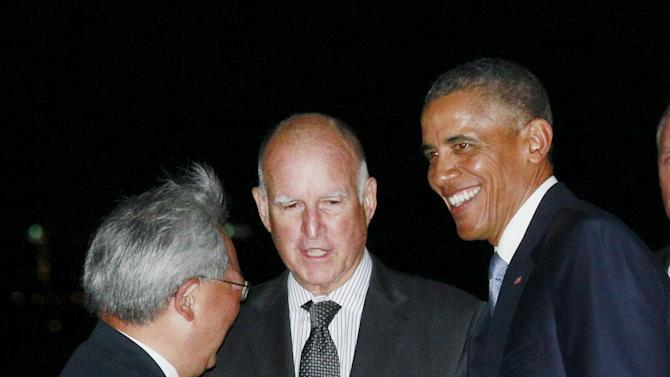 U.S. President Barack Obama is greeted by California Governor Jerry Brown and San Francisco Mayor Ed Lee upon his arrival in San Francisco