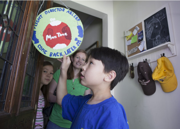 "In this photo taken Tuesday, Aug. 14, 2012,  Devyn Oh, 8, flips around a sign reading: ""Flight Director Sleep on Mars Time, Come Back Later,"" posted on their front door for his father, David Oh, a fli"