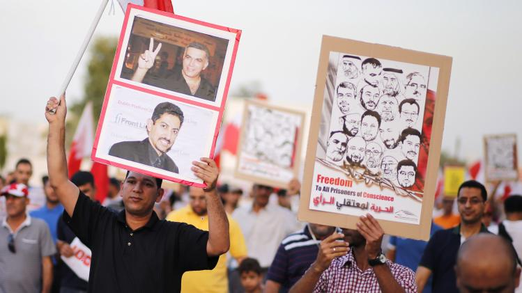 A protester holds a banner with photos of human rights activists Nabeel Rajab and Abdulhadi Al Khawaja as he participates in an anti-government rally in Budaiya