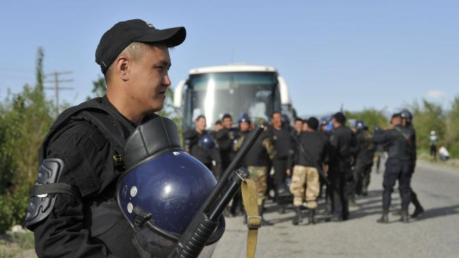Police stand guard outside the Kyrgyz town of Barskoon Friday, May 31, 2013. Hundreds of stone-throwing protesters besieged a Canadian gold mine in Kyrgyzstan on Friday, clashing violently with riot police and prompting the president to declare a state of emergency. Protesters want the northeastern Kumtor gold mine to be nationalized and the company to provide more benefits. (AP Photo/Vladimir Voronin)