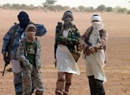 Fighters of the Islamist group Ansar Dine stand in Kidal as Burkina Faso's foreign minister Djibrille Bassole meets with the group's leader on August 7, 2012. One of the main Islamist groups in Mali split Thursday, with the breakaway faction saying it was ready for talks to end a two-week-old French-led offensive, amid mounting concerns over rights abuses by government troops