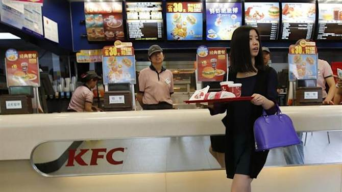 A woman holds food inside a KFC restaurant in Beijing, May 9, 2013. REUTERS/Kim Kyung-Hoon/Files