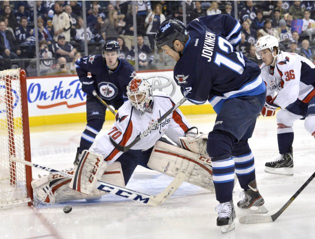 Capitals goaltender Holtby makes a save on Jets' Jokinen during second period NHL game in Winnipeg