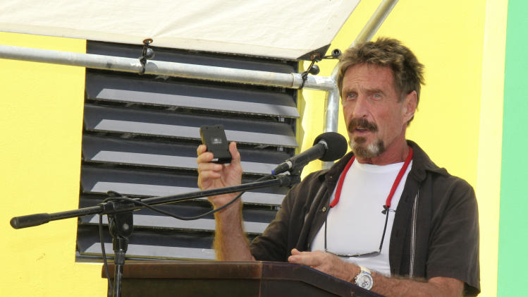 FILE -In this Thursday Nov. 8, 2012 file photo software company founder John McAfee speaks at the official presentation of equipment ceremony that took place at the San Pedro Police Station in Ambergris Caye, Belize.  Software company founder John McAfee said Tuesday, Nov. 20, 2012, he's wearing a disguise and hiding in plain sight, watching police and reporters stake out his home and blogging about it.  (AP Photo/Ambergris Today Online-Sofia Munoz, File)
