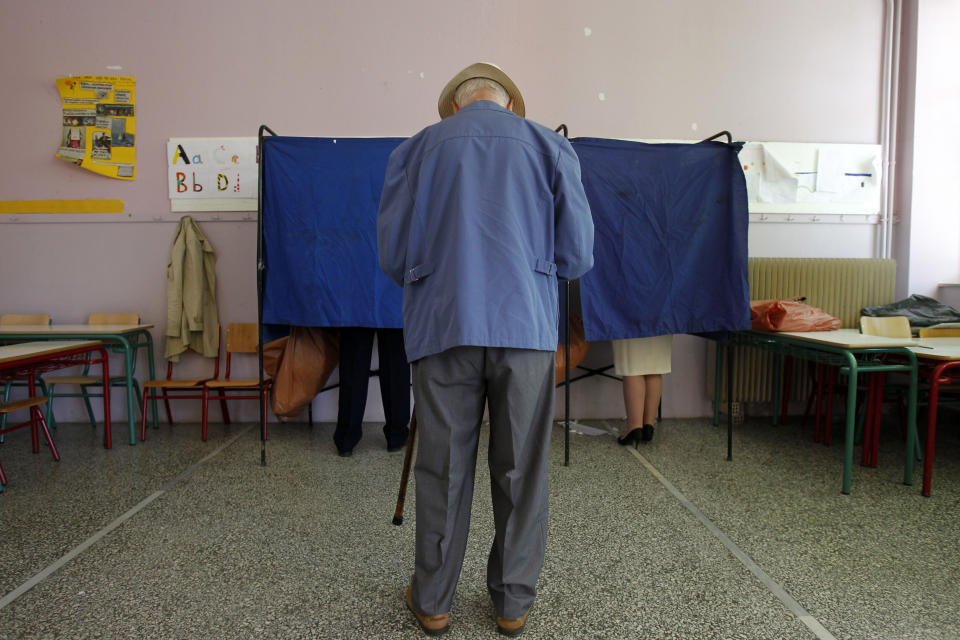 A man waits to enter a voting booth at a polling station in Athens, Greece, Sunday May 6, 2012. Greeks casted ballots on Sunday in their most critical - and uncertain - election in decades, with voters set to punish the two main parties that are being held responsible for the country's dire economic straits. (AP Photo/Kostas Tsironis)