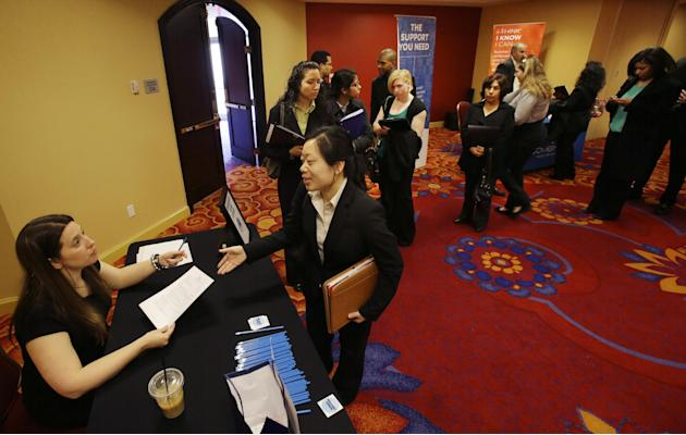 In this Tuesday, Feb. 26, 2013, photo, a line of people wait, as Neely Raffellini, left, helps job seekers revise their resumes during the Edison Career Fair job fair in the Iselin section of Woodbrid