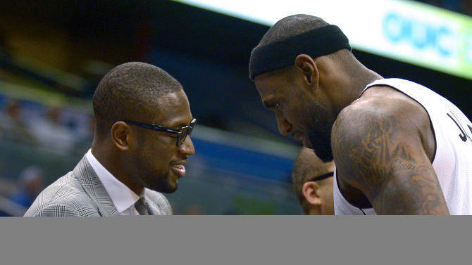 Miami Heat forward LeBron James, right, is congratulated by teammate Dwyane Wade after James exited the game late in the second half of an NBA basketball game against the Orlando Magic in Orlando, Fla., Monday, March 25, 2013. The Heat won 108-94. (AP Photo/Phelan M. Ebenhack)