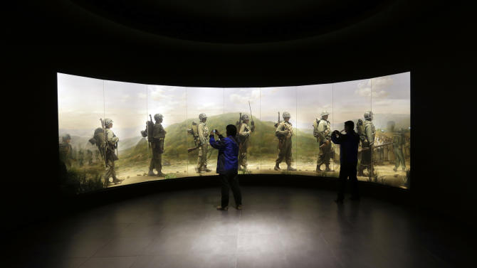 Visitors take souvenir pictures in front of an exhibit depicting South Korean soldiers during the Korean War at the Korea War Memorial Museum in Seoul, South Korea, Wednesday, March 6, 2013. North Korea's military is vowing to cancel the 1953 cease-fire that ended the Korean War, straining already frayed ties between Washington and Pyongyang as the United Nations moves to impose punishing sanctions over the North's recent nuclear test. (AP Photo/Lee Jin-man)