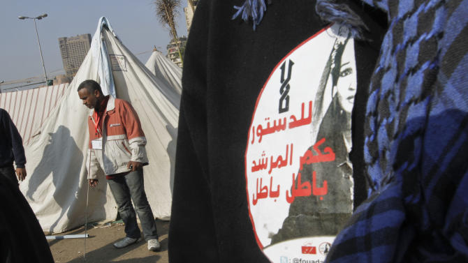 """A protesters wears a sticker with Arabic that reads, """"no to the supreme guide's rule, void, void,"""" in Tahrir Square, the focal point of the Egyptian uprising, in Cairo, Sunday, Dec.16, 2012. Key Egyptian rights groups called Sunday for a repeat of the first round of the constitutional referendum, alleging the vote was marred by widespread violations. Islamists who back the disputed charter claimed they were in the lead with a majority of """"yes"""" votes. (AP Photo/Amr Nabil)"""
