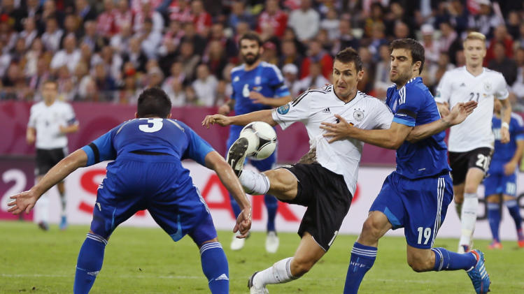 Germany's Miroslav Klose, center, gets the ball past Greece's Giorgos Tzavelas, left, and Sokratis Papastathopoulos during the Euro 2012 soccer championship quarterfinal match between Germany and Greece in Gdansk, Poland, Friday, June 22, 2012. (AP Photo/Frank Augstein)
