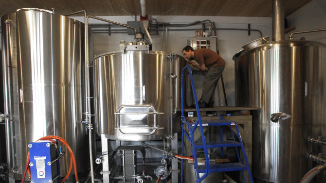 In this Wednesday, April 3, 2013 photo, brewer Shaun Hill checks a batch of beer at Hill Farmstead Brewery in Greensboro, Vt. Vermonters are buzzing about beer, and with good reason. The craft brew world has noticed that the small New England state better known for its cheeses and maple syrup also happens to make killer beer. In fact, one brewery, Hill Farmstead Brewery, has been rated the world's best brewer on a popular international consumer review website called RateBeer.com. (AP Photo/Toby Talbot)