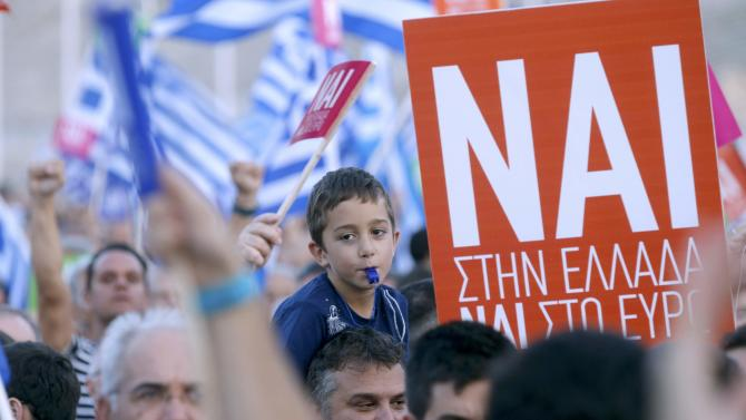 A young 'Yes' supporter blows a whistle during a pro-Euro rally in front the Panathenean stadium in Athens