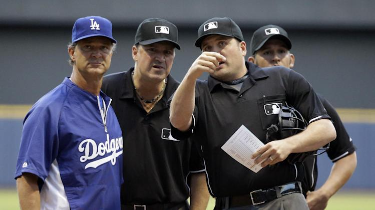 Los Angeles Dodgers manager Don Mattingly looks over Miller Park with the umpires before a baseball game against the Milwaukee Brewers Monday, May 20, 2013, in Milwaukee. (AP Photo/Morry Gash)