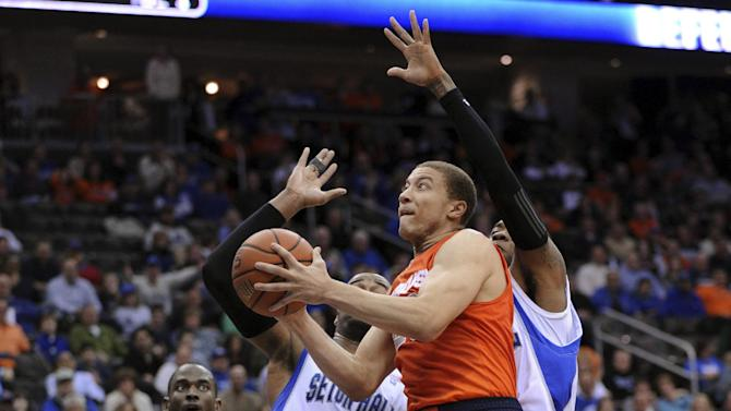 Syracuse's Brandon Triche goes up for a shot as Seton Hall's Eugene Teague, left, and Fuquan Edwin, right, defend during the first half of an NCAA college basketball game Saturday, Feb. 16, 2013, in Newark, N.J. (AP Photo/Bill Kostroun)