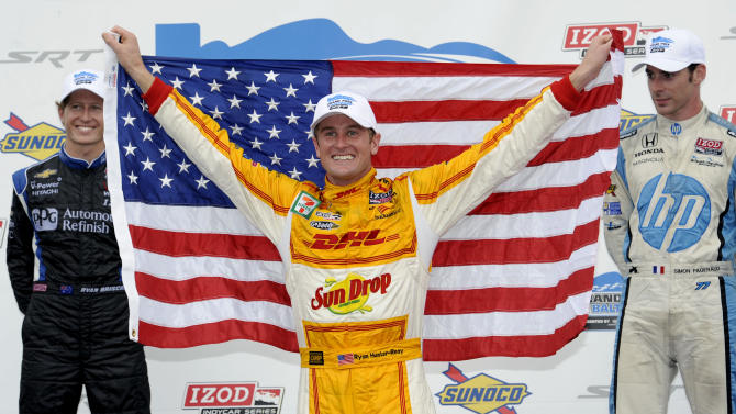 Ryan Hunter-Reay celebrates in victory lane after winning the IZOD IndyCar Grand Prix of Baltimore auto race, Sunday, Sept. 2, 2012, in Baltimore. At left is runner up Ryan Briscoe, of Australia, and at right is Simon Pagenaud, of France, third place finisher. (AP Photo/Nick Wass)
