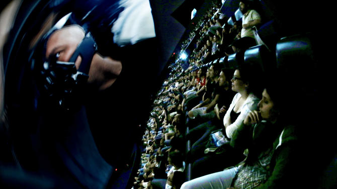 """In this photo taken with a fisheye lens, people watch villain Bane on the screen during the midnight premiere of """"The Dark Knight Rises"""" inside the Liberty Science Center IMAX theater Friday, July 20, 2012, in Jersey City, N.J. A gunman in a gas mask barged into a crowded Denver-area theater during a midnight premiere of the Batman movie on Friday, July 20, 2012, hurled a gas canister and then opened fire, killing 12 people and injuring at least 50 others in one of the deadliest mass shootings in recent U.S. history. (AP Photo/Julio Cortez)"""