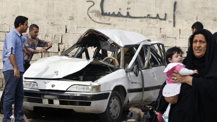 People inspect a damaged car at the scene of a car bomb attack in Zayona neighborhood of eastern Baghdad, Iraq, Wednesday, March 20, 2013. Iraqi officials say a car bomb in eastern Baghdad has killed and wounded a few people on the 10th anniversary of the US-led invasion, the day after a series of well-coordinated attacks left scores dead. (AP Photo/Hadi Mizban)