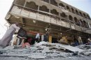 People gather at site of car bomb attack in Baghdad's al-Shaab district