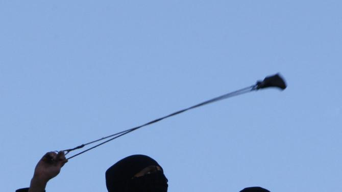 Palestinian uses a slingshot to hurl stone at Israeli soldiers during clashes in the West Bank city of Hebron